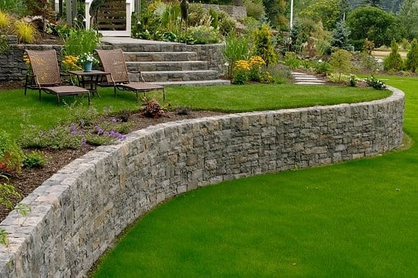 curved retaining wall with green grasss
